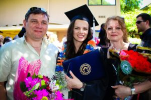 Adriana with her parents at graduation