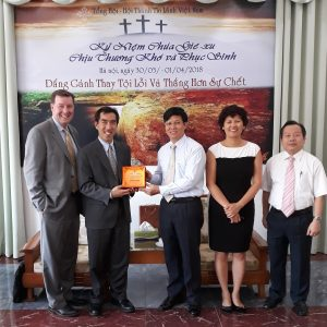 Hien Vu and the IGE team with pastor Nguyen Huu Mac, president of Evangelical Churches of Vietnam-North, a denomination with 1,000 churches throughout northern Vietnam. Pastor Mac gave them a plaque of the Hanoi Bible College (the only formally recognized Protestant college/seminary in the north of Vietnam) which graduated its first students. IGE, among others, engaged the government for many years, arguing that people of faith should be able to teach their own theology which would also produce better citizens that serve the elderly and orphans while providing a moral bulwark against corruption..